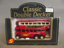 A boxed Corgi model of a classic double decker bus bearing the 'Holy Time News' banner