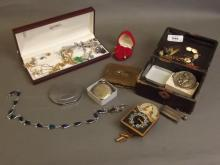 A quantity of costume jewellery including a miniature clock, a watch case, compacts etc