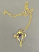 A 9ct gold pendant set with a central amethyst