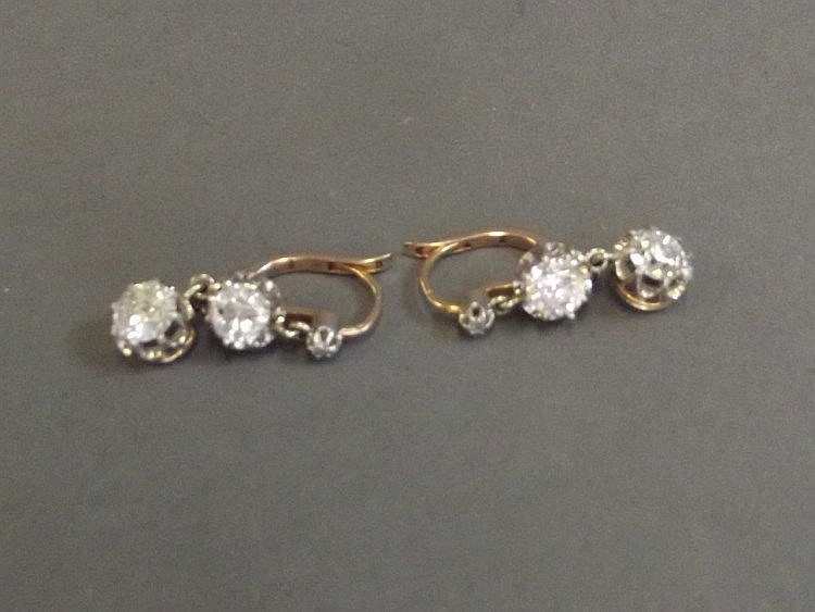 An unmarked gold pair of diamond drop earrings,