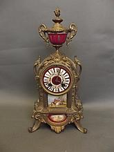 A large brass mantle clock with puce ground
