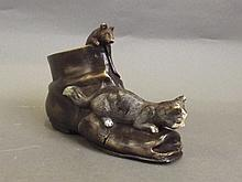 A cold painted bronze boot surmounted by a cat and