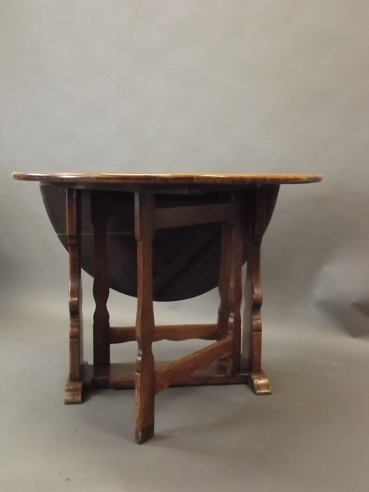 An oak drop leaf dining table raised on shaped end supports for Dining table support