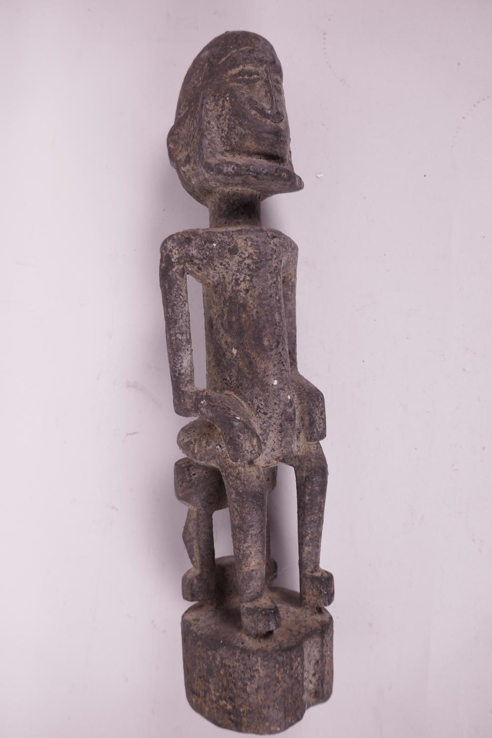 An African carved wood ceremonial figure of a seated man, possibly