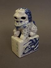 A Chinese blue and white pottery seal in the form of a Fo dog with landscape and character decoration, 4¼'' high