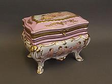 A large Continental pink and white ground pottery casket decorated with winged cherubs and gilt highlights, 11'' x 7¾'', 9'' high