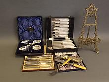 A boxed set of plated butter knives, cake forks and spoons, a boxed set of table salts and spoons, dessert knives and forks, and gilt metal easel frame, 14'' high