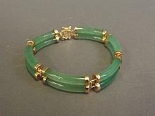 A Chinese apple jade and gilt metal bracelet, 7'' long