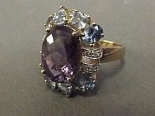 A 9ct gold oval amethyst, blue topaz and diamond cocktail ring, size T