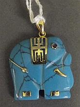 A carved turquoise and yellow metal pendant in the