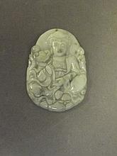 A Chinese carved jade pendant depicting a deity,