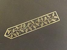 A silver bookmark with cut leaf design, in a