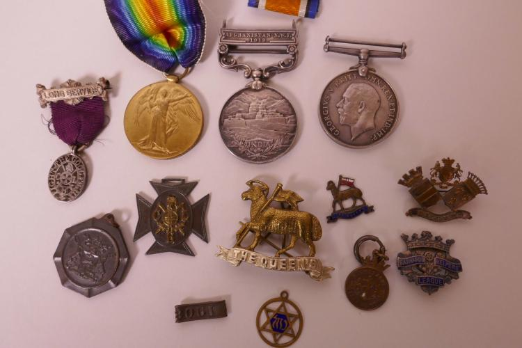 A COLLECTION OF MILITARY MEDALS AND CAP BADGES INCLUDING AN INDIAN SERVICE 1919 AFGHANISTAN NORTHWEST FRONTIER MEDAL, TWO WW1 SERVICE MEDALS, THE QUEEN'S REGIMENT CAP BADGE ETC