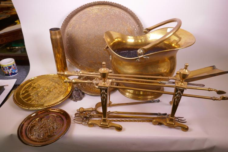 A C19TH HELMET SHAPED BRASS COAL SCUTTLE, FIRE DOGS AND A THREE PIECE BRASS COMPANION SET AND SEVEN EMBOSSED BRASS TRAYS, COMPANION SET 26