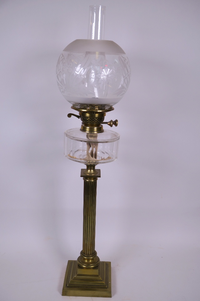 A TALL BRASS CORINTHIAN COLUMN TABLE LAMP WITH STEPPED SQUARE BASE, GLASS FRONT, DUPLEX BURNER, CLEAR GLASS SHADE AND CHIMNEY, 22