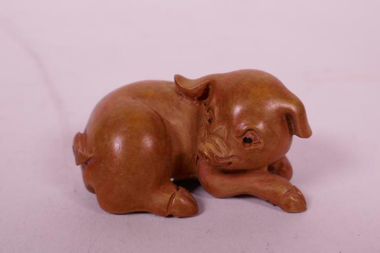 A JAPANESE CARVED BOXWOOD NETSUKE IN THE FORM OF A PIG, 2