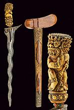 A kris, dating: 20th Century, provenance: Bali, dating: 20th Century, provenance: Bali, Double-edged blade made of pamor, grooved and carved at the base; bone grip, richly carved in the shape of a deity; gilded-brass mendak, decorated with colored,