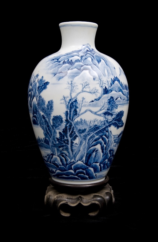 Chinese Blue & White Porcelain Vase.  River & mountains decoration. 6 character mark to base. On carved wood stand.
