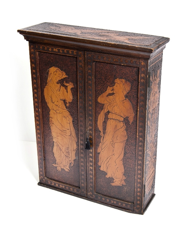 Australian Colonial Pokerwork Pipe & Tobacco Cabinet. 2 doors, figure decorated, opening to fitted & decorated interior with shelves over 2 drawers; inscribed 1896. Key available.