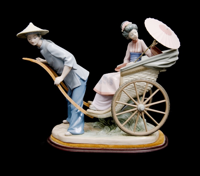 Lladro Woman & Rickshaw Man Figure.  On felt topped wooden stand. (Thumb of woman's hand broken & piece available for restoration).