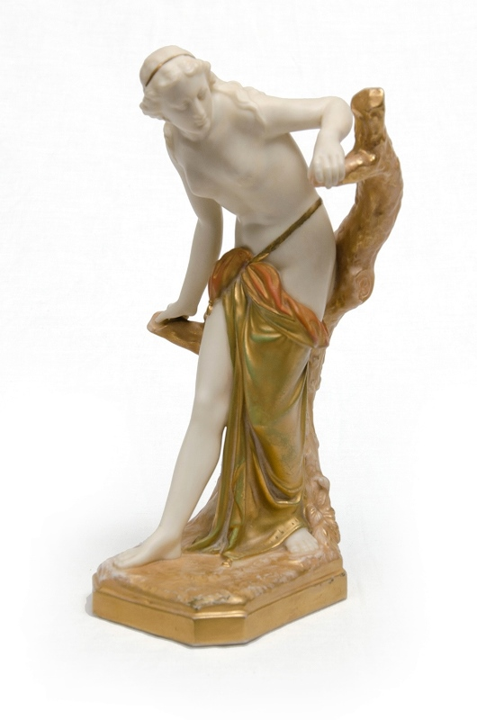 Royal Worcester Classical Woman Figure.  Nude leaning on a tree branch. White/cream porcelain with extensive gilt highlights. Significant wear to gilt on drape and base. Marked to base #486. c1918.