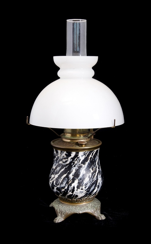 Early Metal Fuel Lamp. Ceramic covered brass base on 4 paw feet. With original white glass shade & glass chimney.