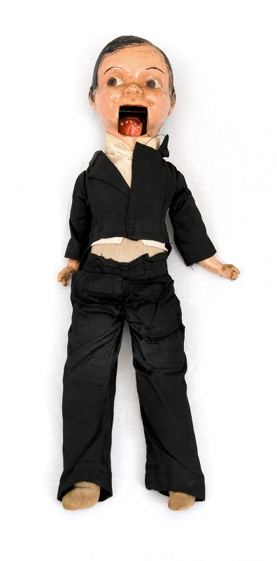 Early Ventriloquists Doll.  Composition head. Fabric body. Boy dressed in black jacket & trousers. Mouth aparatus needs repair.