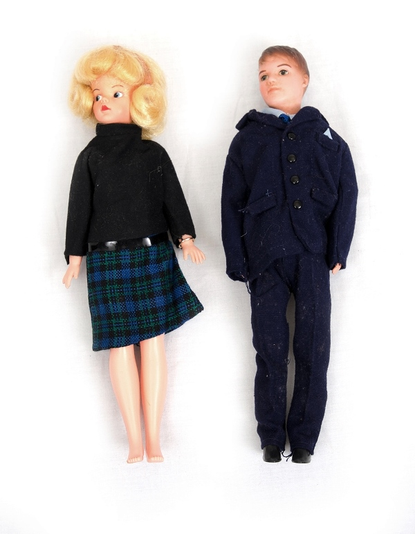 Pr Plastic Dolls.  Young couple Blonde woman in tartan skirt; & young man in navy blue jacket & trousers.