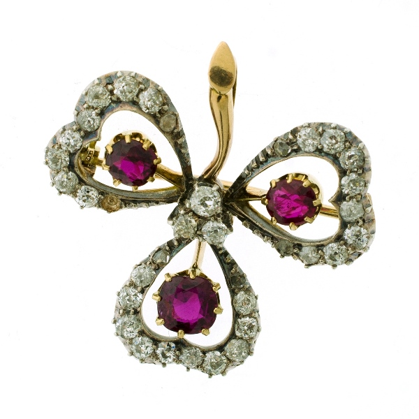 Yellow Gold Ruby & Diamond Clover Leaf Brooch.  Set with 3 rubies (total approx. 3cts) each surrounded by diamonds, with 3 central diamonds (1 diamond missing). Silver setting.