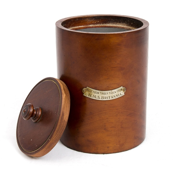HMS Britannia Tobacco Jar.  Lidded mahogany canister with engraved metal label 'Made from timber taken from HMS Britannia.' Metal lined interior.