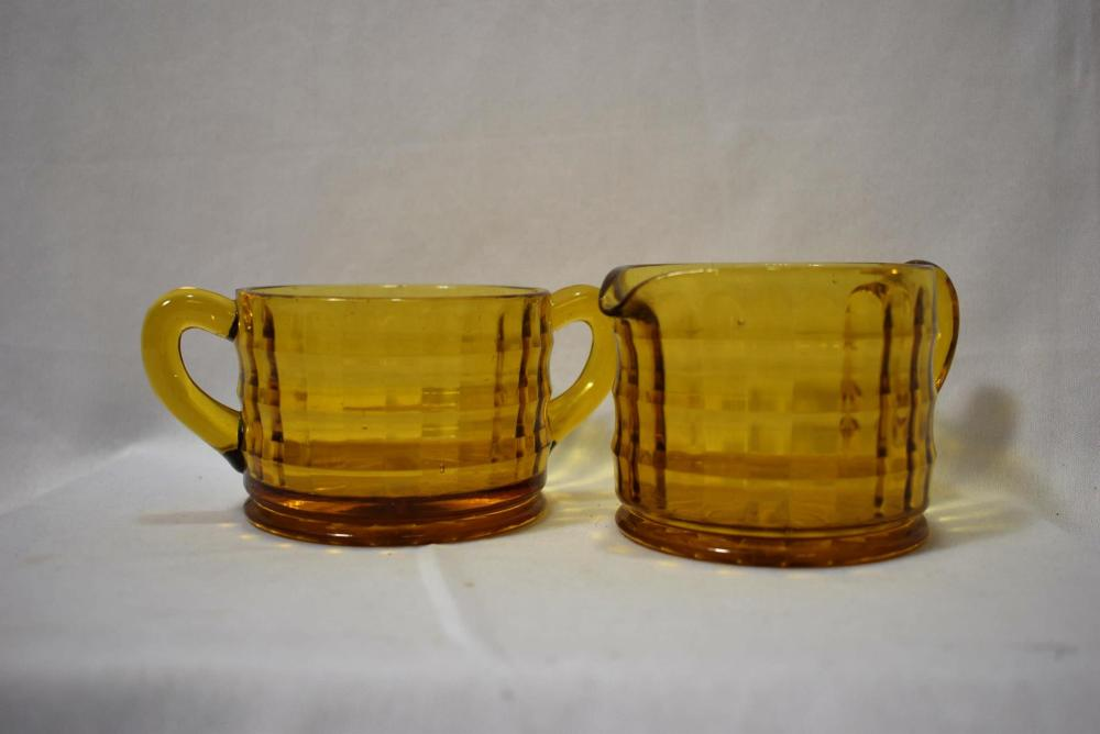 An Amber Glass Set of Cream and Sugar Container