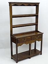 An early 20thC oak Dresser of small proportions with two tier plate rack having a shaped frieze and eight hanging hooks, the base having two short drawers and a shaped apron, standing on block legs. 40 ½'' wide x 14'' deep x 66 ½'' high.