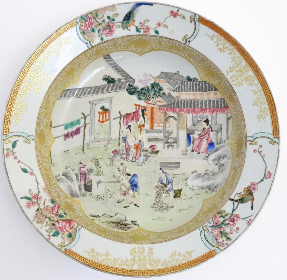 A large Chinese bowl with hand painted scenes of rural life, including a mother and child, figures f