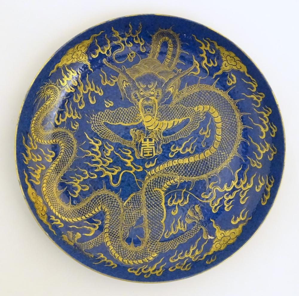 A Chinese dish decorated with a gilt dragon on a blue ground. Approx. 10 1/4'' diameter.
