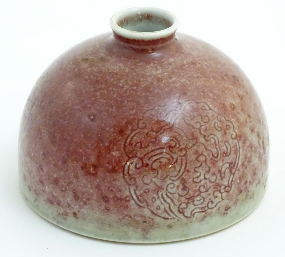 A Chinese sang-de-boeuf pot/taibai zun formed as a dome, decorated with three stylised dragon rounde