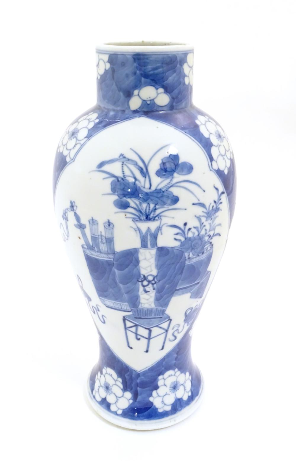 A Chinese, blue and white baluster vase decorated with prunus flowers, the central decoration displa