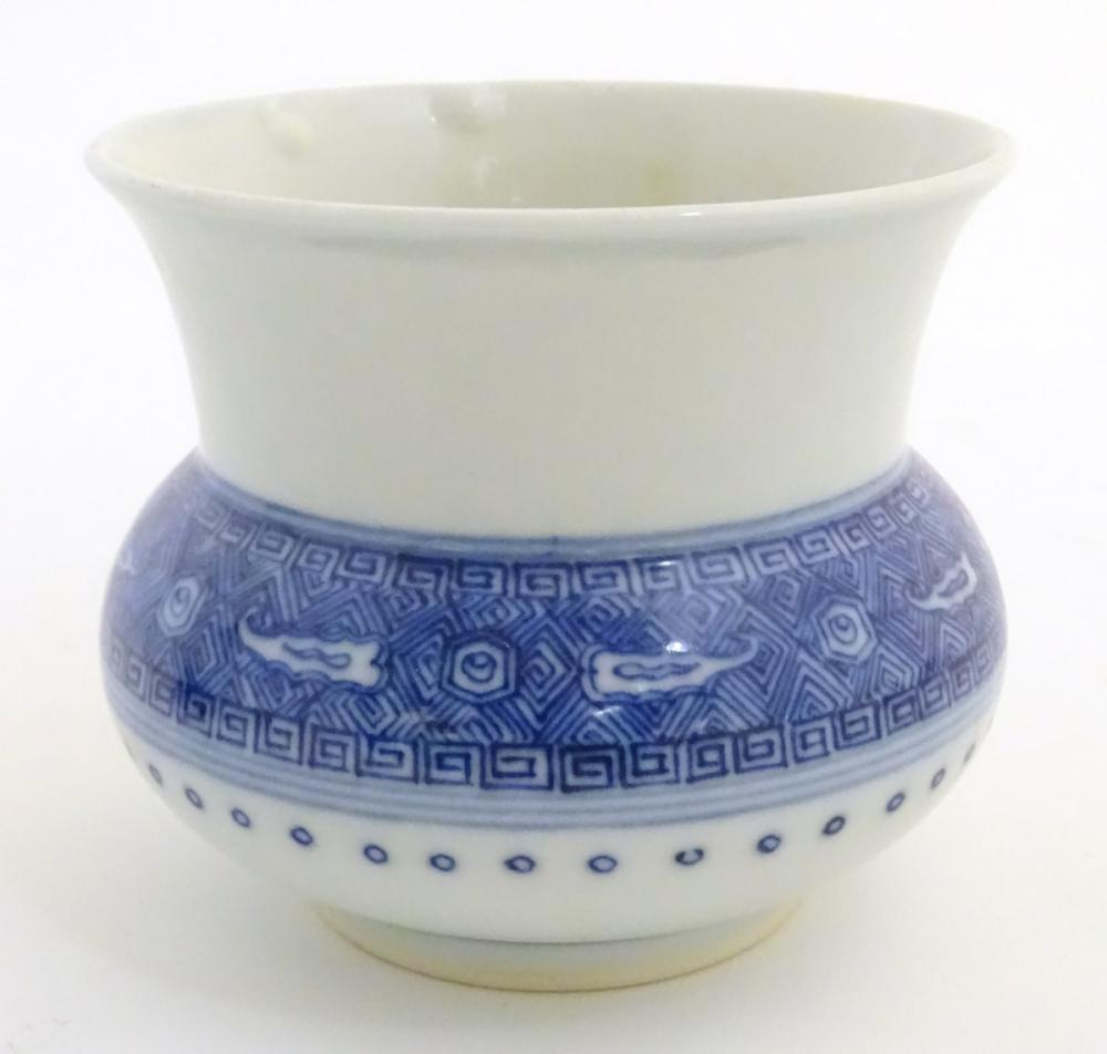 A Chinese pot/vase of squat form, with a round body and a flared rim. Decorated with banded geometri
