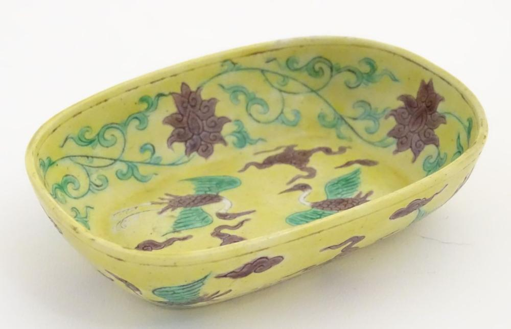 A small Chinese dish decorated with stylised birds, clouds and flowers. Character marks to base. App