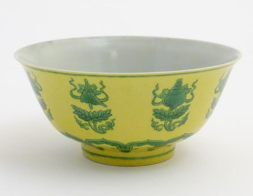 A Chinese bowl decorated with green auspicious motifs above scrolling lotus flowers on a yellow grou