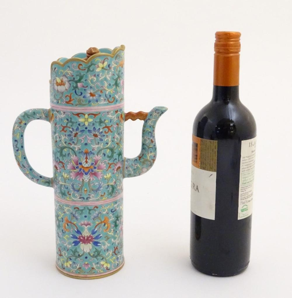 A Chinese famille rose, Tibetan style tubular lidded wine ewer with a scrolling lotus design on a tu