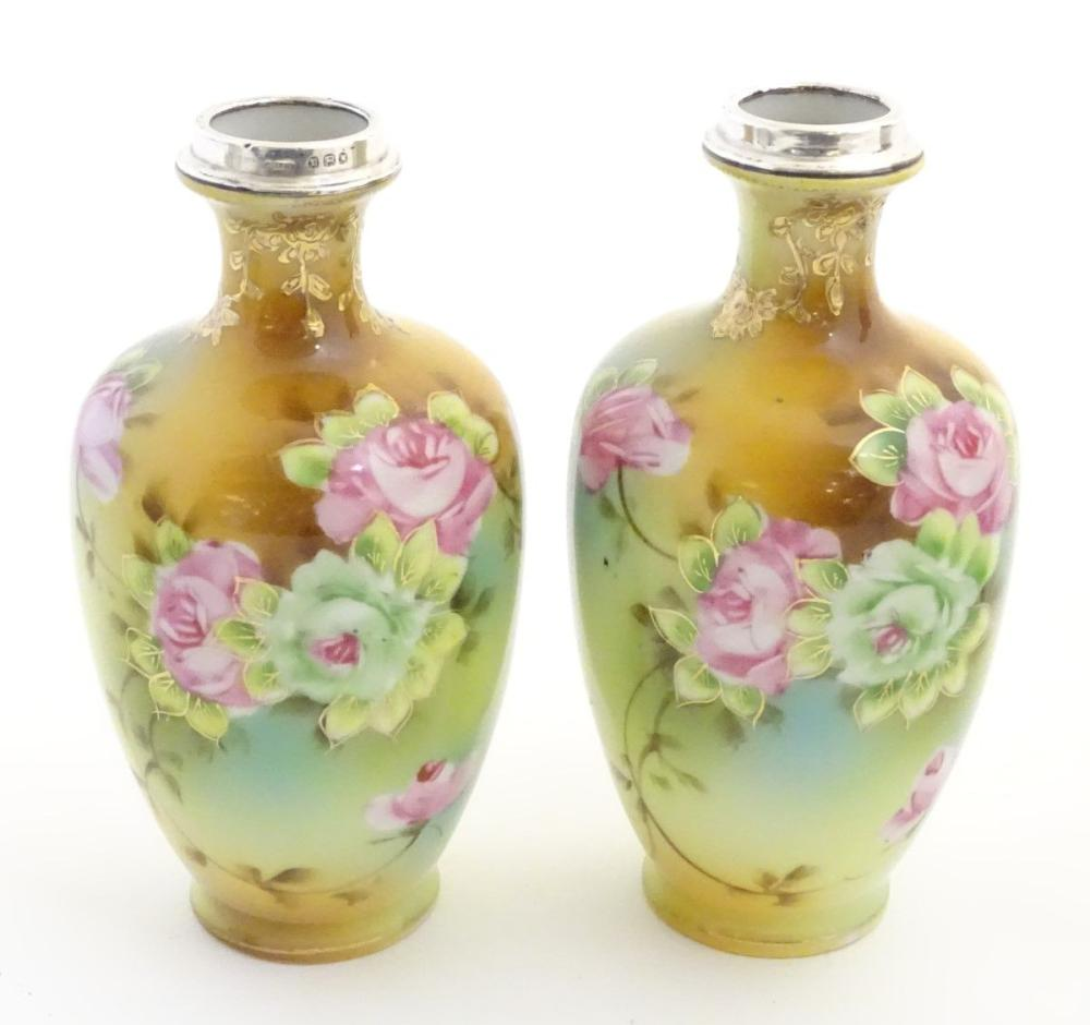 A pair of small Japanese baluster vases with hand painted floral decoration, gilt highlights and sil