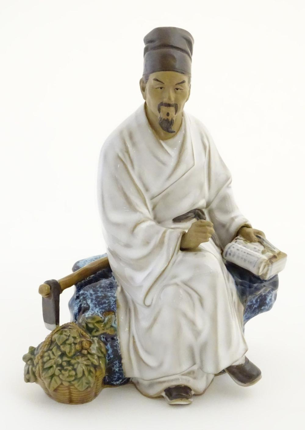 A Chinese partially glazed ceramic mudman figurine depicting a scholar/scribe, thought to be Chung K