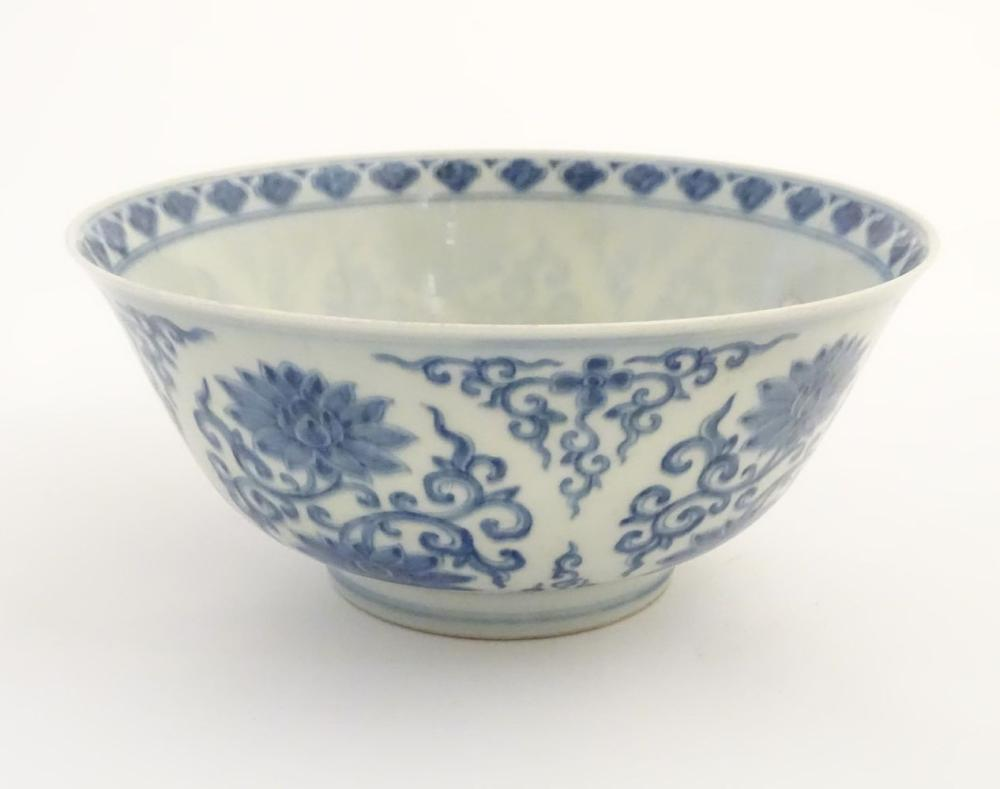 A Chinese blue and white bowl decorated with flowers and scrolling vines. Character marks to base. A