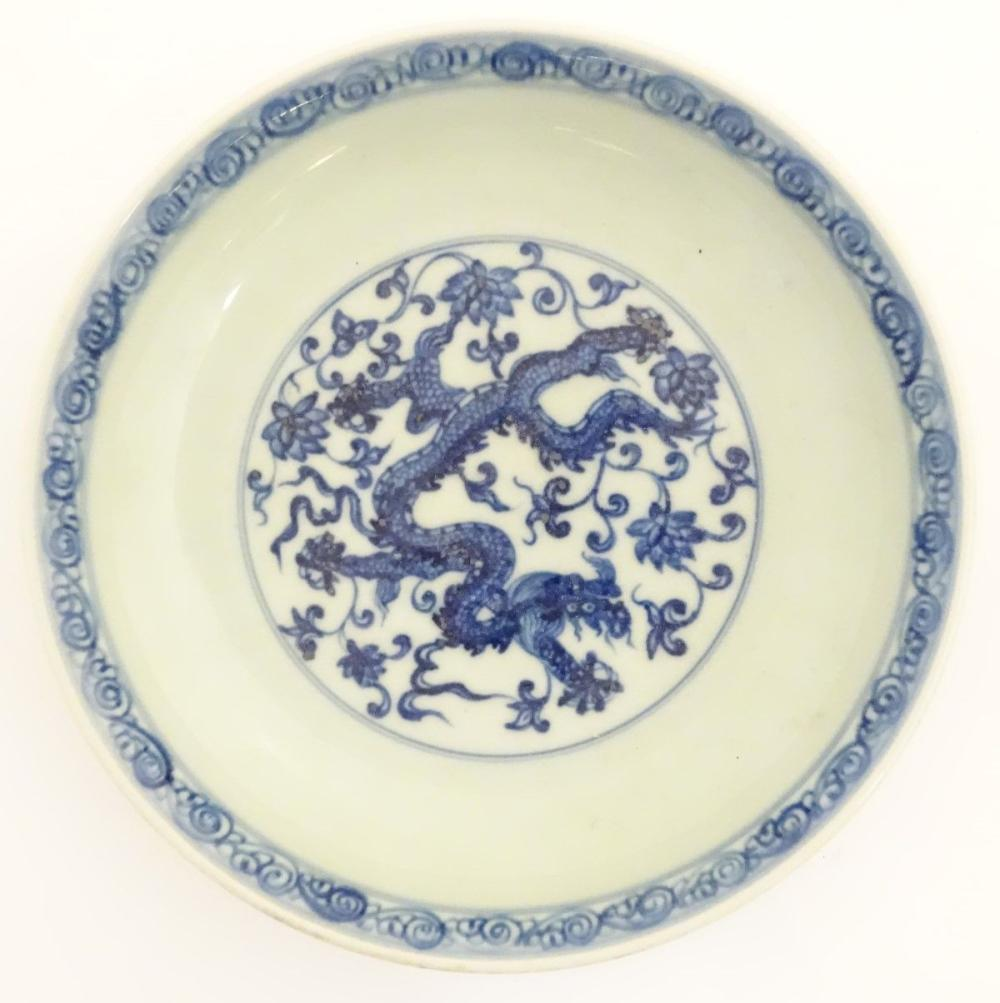 A Chinese blue and white dish decorated with dragons, and scrolling flowers. Character marks to base