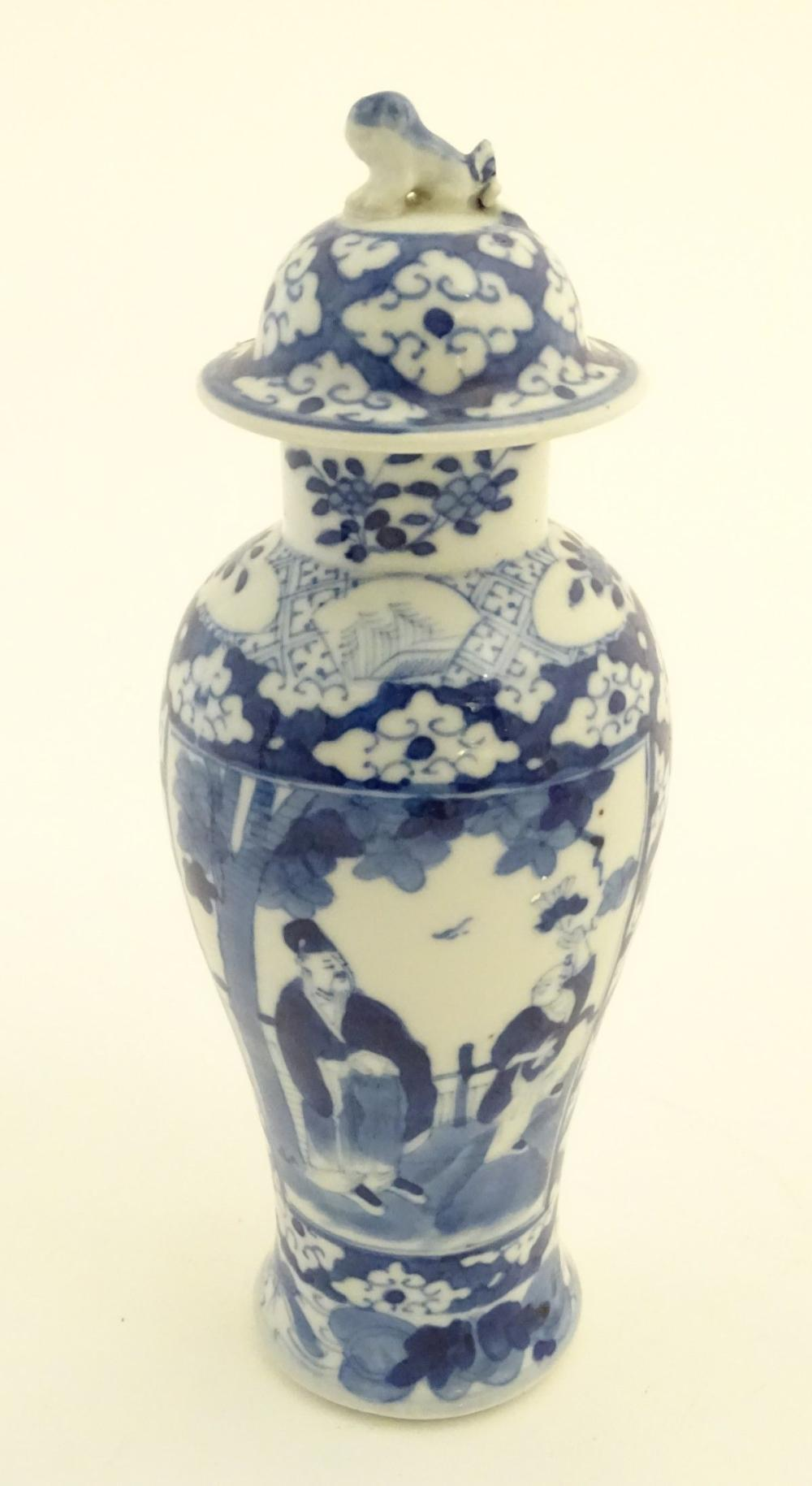 A Chinese blue and white ginger jar decorated with a floral pattern and two panels depicting an elde