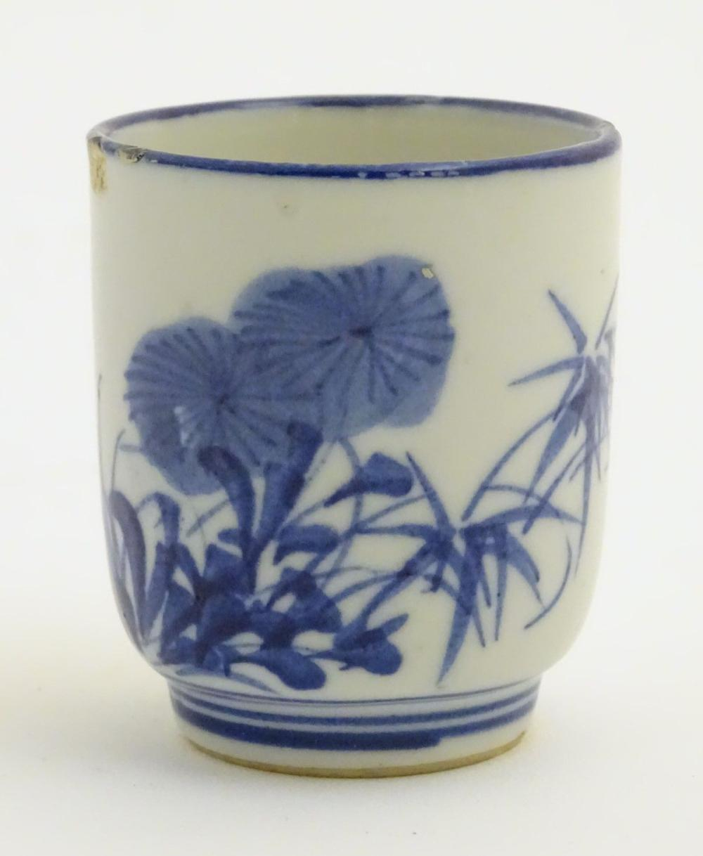 A Japanese blue and white pot with hand painted floral and foliate decoration. Character marks to ba