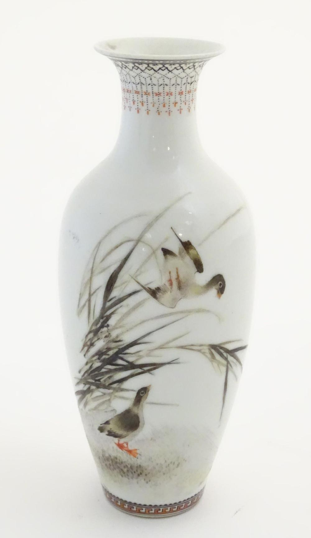 A small Oriental baluster vase, decorated with wader birds in reeds, with calligraphy to the reverse