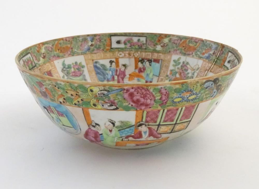 A Cantonese famille rose bowl with panelled decoration depicting figures in traditional dress in var