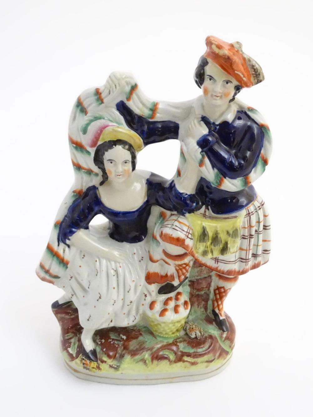 A Victorian Staffordshire pottery figural group of a man and a woman in highland dress, he is wearin