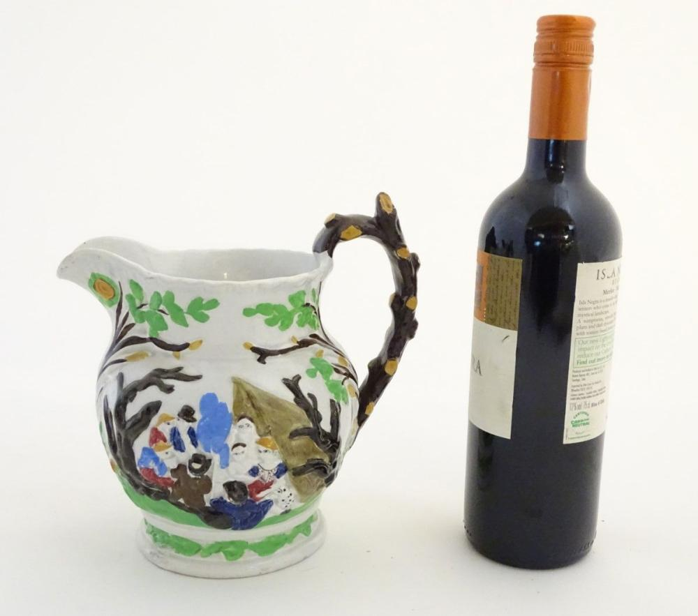 A 19thC Staffordshire Pottery Pratt style jug, depicting figures in a landscape with dogs, a horse,